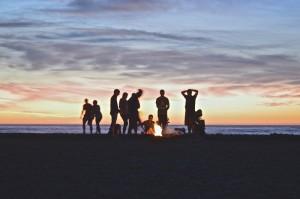 friends-relaxing-around-bonfire-on-beach-at-sunset